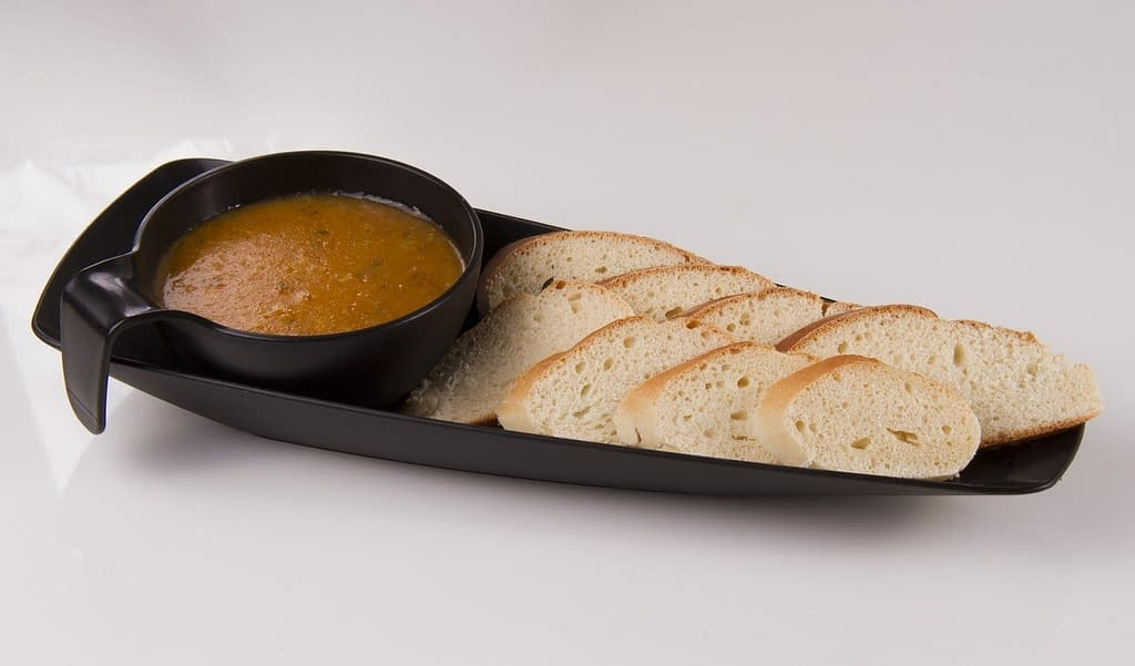 black tray with soup and slices of bread